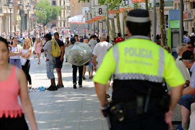 Un guàrdia urbà sacosta a uns manters al Portal<BR/>de lÀngel, ahir.