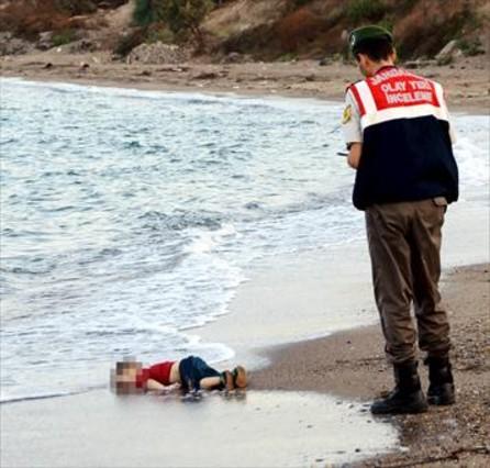El niño sirio Aylan Kurdi, ante un guardacostas en la playa de Turquía a la que llegó su cadáver.