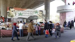 Sirios pasean por un mercado de Damasco tras el alto el fuego en Siria.
