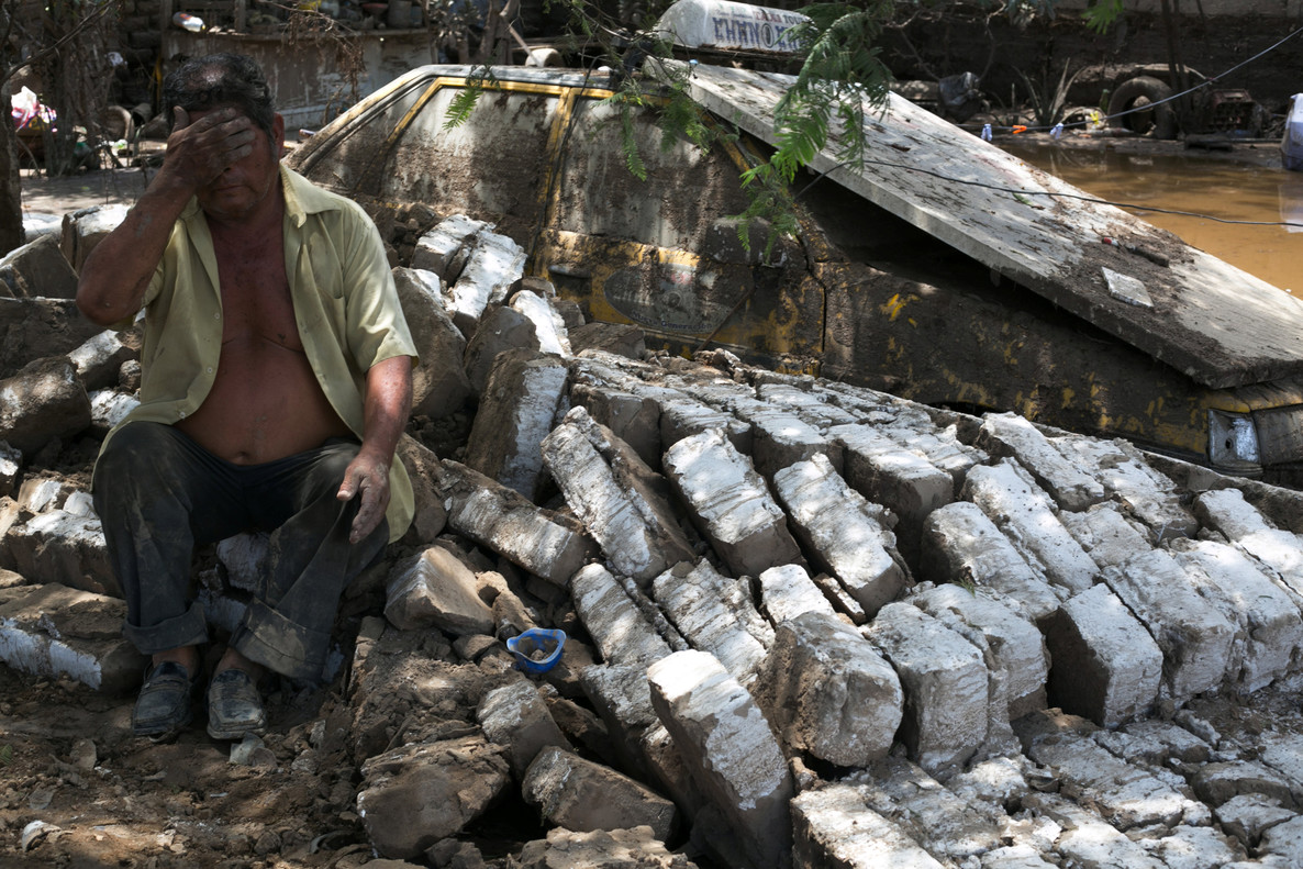 A man sits next to debris of his home, destroyed after rainfall and flood in Trujillo, northern Peru,
