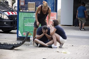 Tres jóvenes, en la Rambla, junto a la furgoneta utilizada para el atentado.