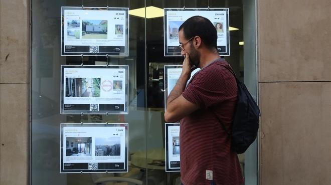 Un joven mirando ofertas de pisos de alquiler en los expositores de una inmobiliaria de Barcelona.