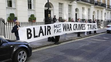 """Manifestantes frente a la casa de Tony Blair con la pancarta """"Blair debe hacer frente a un juicio por crímenes de guerra""""."""