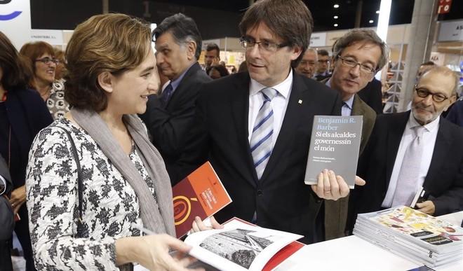 Carles Puigdemont le muestra a Ada Colau, durante la inauguración de Liber, el libro 'Si els alcaldes governessin el món'