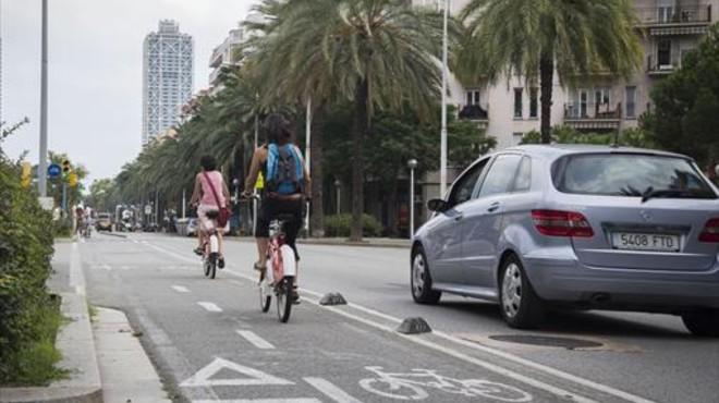 Dos ciclistas circulan por el carril bici de dos direcciones de la calle de Marina.