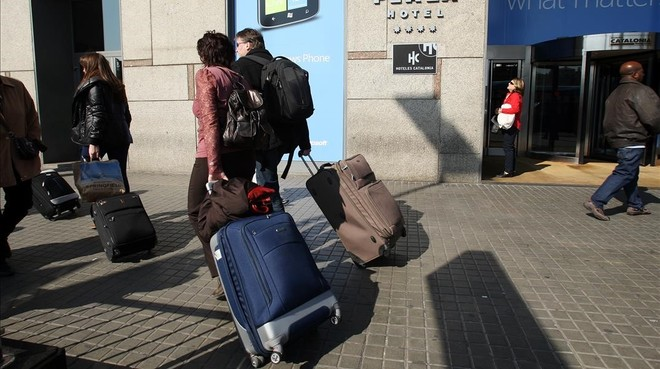 Turistas con la chaqueta sobre la maleta el último fin de semana de febrero en Barcelona.