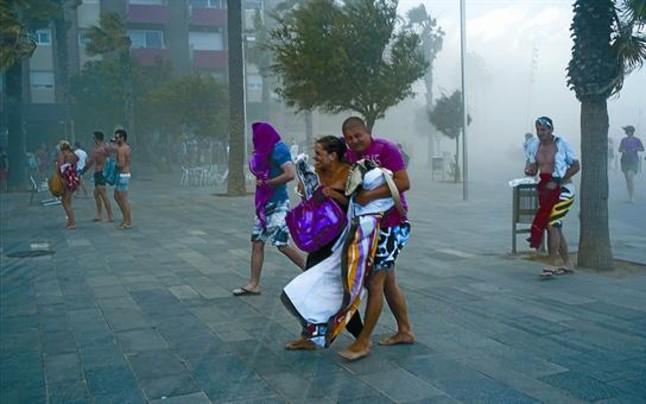 BRUMA EFÍMERA 3 Numerosos bañistas abandonan las playas del sector de la Barceloneta, ayer a última hora de la tarde, al tiempo que intentan protegerse del impacto de la nube de arena que levanta el súbito vendaval. VICENS FORNER