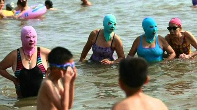 Mujeres con facekini en una playa de China.