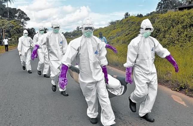Personal protegido con trajes especiales retira el cuerpo de un fallecido por ébola en Monrovia (Liberia), el sábado.