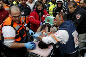 Israeli medics evacuate a wounded person from the scene of a shooting incident in Tel Aviv