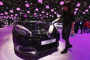 Una empleada limpia un Renault en el Salón de Bruselas.