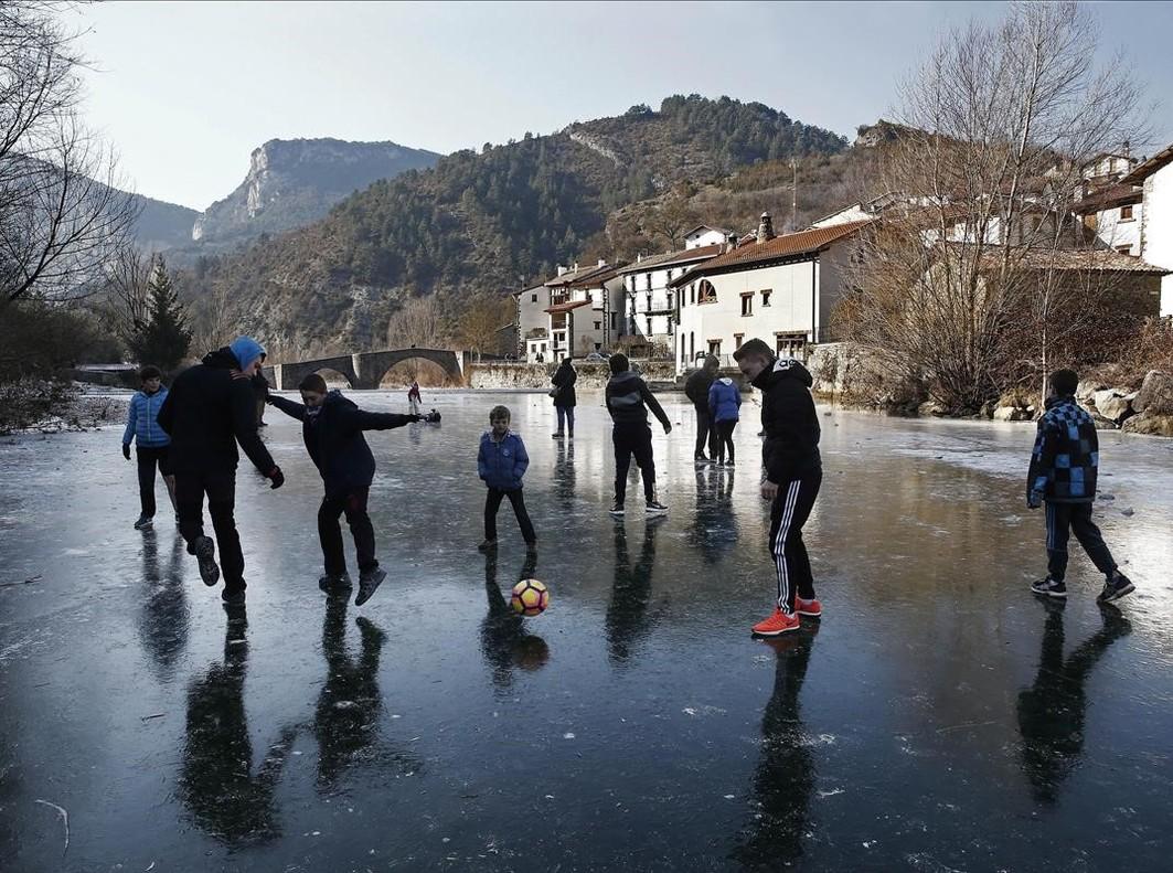 Un grupo de jovenes juegan a fútbolsobre la superficie helada del Rio Esca a su paso por la localidad navarra de Burgui.