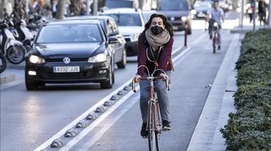 Ciclista circulando en bicicleta por el carril bici de Diagonal protegida por una mascarilla antipolución.