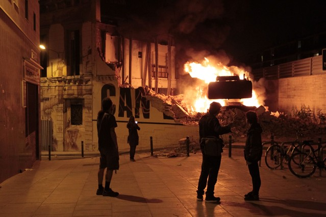 Un grupo de personas observa la excavadora ardiendo en Can Vies.