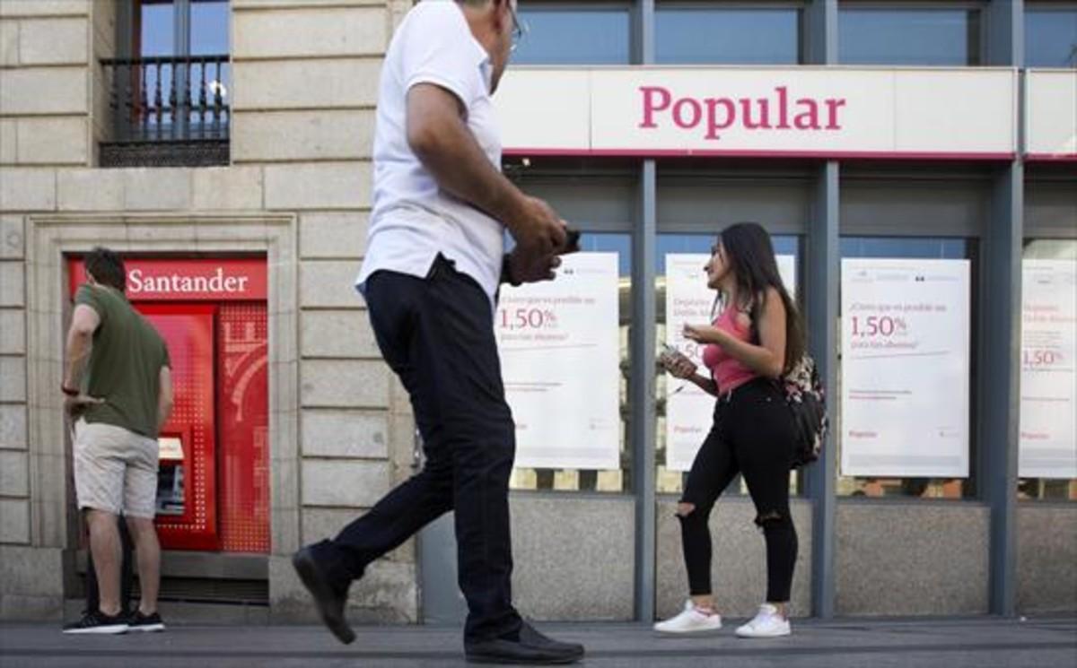 Un cajero automático del Santander junto a una sucursal del Popular en Madrid, ayer.