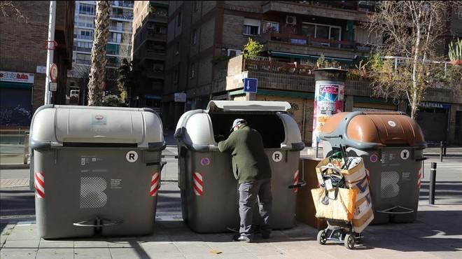 Un hombre rebusca en un contenedor.