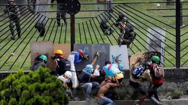 Manifestantes protegiendose delas fuerzas de seguridad antidisturbios en la valla de una base aérea en las protestas contra el presidenteNicolás Maduro, en Caracas, Venezuela.