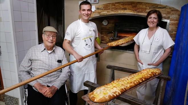 Jaume, Enric y Anna en el obrador del Forn Elias, frente al horno en el que en Navidad aún cuecen pollos.