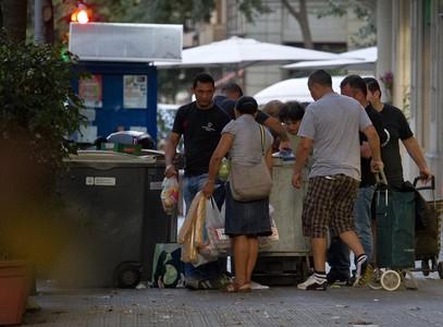 Un grupo de ciudadanos cogen comida caducada de un contenedor de un supermercado, en Barcelona.