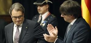 Artur Mas recibe el aplauso de Carles Puigdemont en la toma de posesión en la Generalitat.