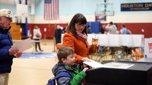 Una mujer con su hijo vota en las primarias en un gimnasio escolar de Concord (Nuevo Hampshire), este martes.