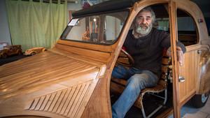 El carpintero francés Michel Robillard posa orgulloso dentro de su Citroën 2CV de madera.