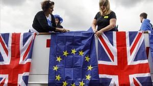 Un grupo contrario al brexit cuelga banderas británicas y de la UE junto al Támesis, en Londres.