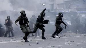 Policías lanzan botes de gas lacrimógeno contra los manifestantes que les lanzaron piedras y latas en las inmediaciones del Congreso, en Buenos Aires, el 14 de diciembre.