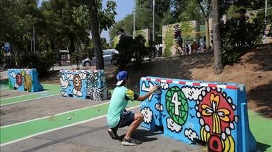 Kamil Escruela, en el aparcamiento del parque G�ell, da unos repasos a una de sus obras.