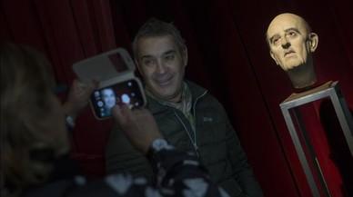Un visitante se fotograf�a junto a la inquietante testa cedida por el artista Eugenio Merino.