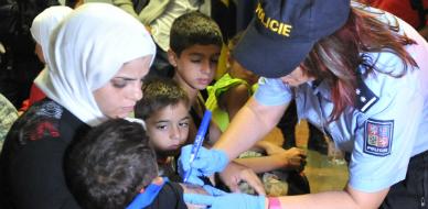 La polic�a checa marca con n�meros a los refugiados
