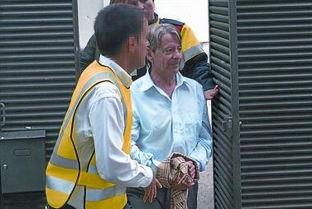Josep Xicola sale de su casa en Cabrils, ayer, escoltado y con las esposas tapadas con una bufanda.
