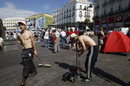 Unos jóvenes limpian en la Puerta del Sol.