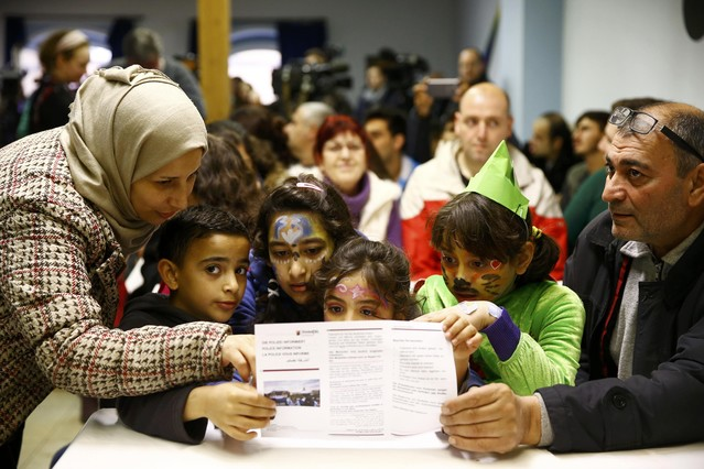Syrian family read information leaflets on social etiquette ahead of the carnival season at refugee camp in Mainz