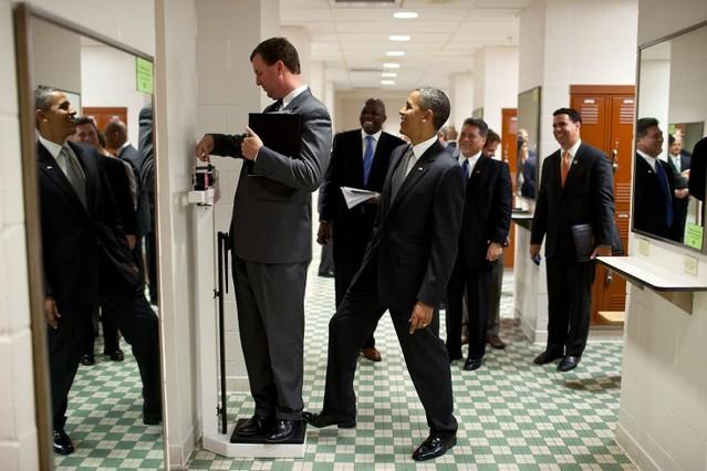 Marvin Nicholson, director de viajes del presidente, se pesa en una báscula mientras Obama bromea con él, en agosto del 2010.