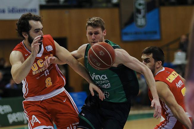 El escolta esloveno del Joventut Luka Lapornik (c) lucha un balón con los jugadores del UCAM Murcia Víctor Benite (i) y el argentino Facundo Campazzo.