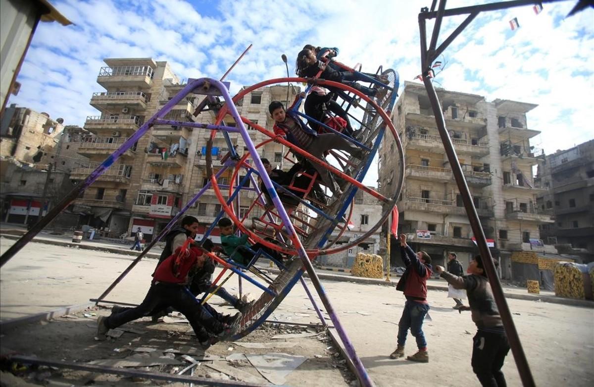 Niños jugandoen un columpio en un barrio de la ciudad síria deAlepo.