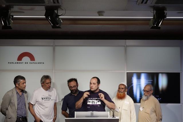 David Fernàndez (CUP), David Companyon (ICV) y Oriol Amorós (ERC), junto a ldos de los paquistanís que fueron condenados, este miércoles en el Parlament.