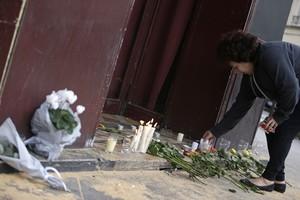 Una mujer deja velas y flores en la puerta del bar Carillon, situado en el décimo distrito de París.
