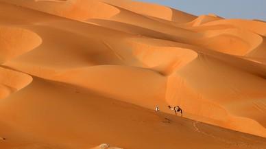 Un hombre camina con su camello por las dunas del desierto de Liwa en elemirato del Golfo de Abu Dhabi.