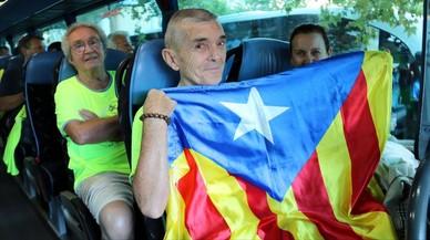 Un home amb una estelada dins d'un autocar que ha sortit del Camp d'Esports de Lleida per anar cap a Barcelona. LAURA CORTÉS / ACN