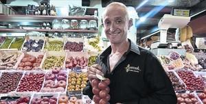 Juan Carlos Torrent, con tomates para untar, en su puesto del mercado de Santa Caterina.