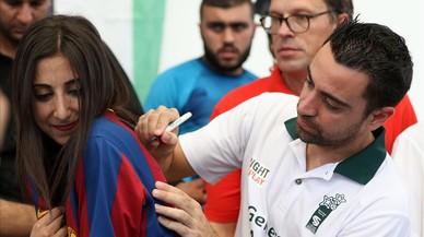 Xavi firma un aut�grafo en la camiseta de una joven, este jueves en el campo de refugiados de Baqa.