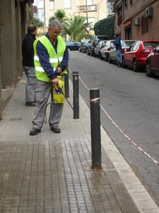 Un operario aplicando el lquido antideslizante en una calle de Santa Coloma de Gramenet.