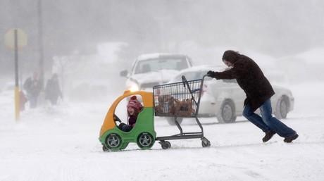 Una mujer arrastra el cochecito de su hijo y el carro de la compra en Saginaw, Michigan.