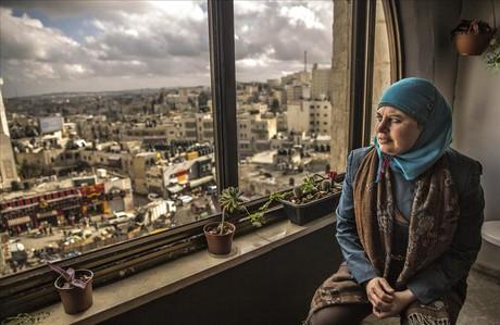 Manal Tamimi mira por el ventanal del hotel que regenta en Ramala.