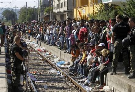 Miles de refugiados esperan un tren que les permita cruzar Macedonia y llegar a Serbia para luego pasar la frontera con Hungría, donde se erige una prolongada valla.