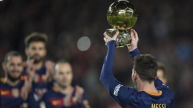 Leo Messi levanta el Bal�n de Oro del 2015 en el Camp Nou, en enero pasado.
