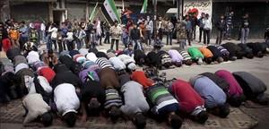 Grupos de sirios rezan durante el segundo aniversario de la revuelta contra el régimen de Asad, este viernes en Alepo.