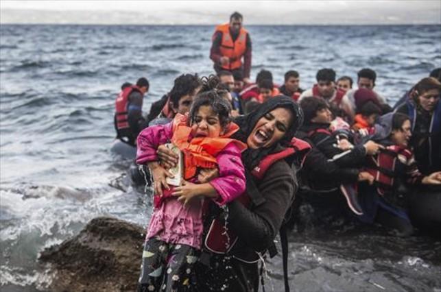 Una refugiada salta de una lancha con un hijo en brazos, en Lesbos.